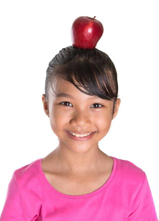 Adolescente femminile con Apple sul suo III capo fotografia stock