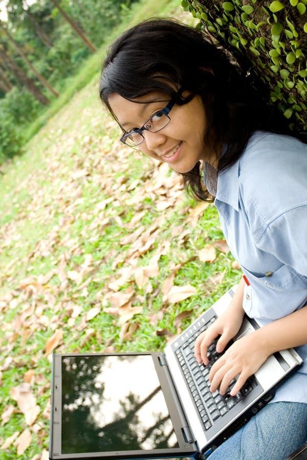 Adolescente femminile con un computer portatile fotografie stock