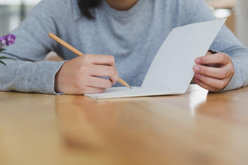 adolescente femminile della ragazza asiatica che studia alla scuola Studente che scrive n immagini stock libere da diritti