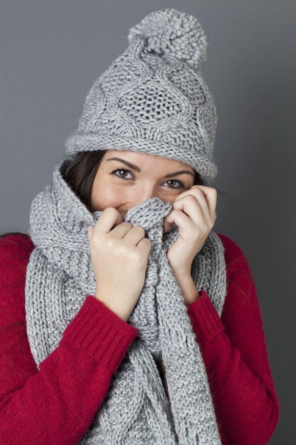 Adolescente femminile felice che sorride nel nascondersi sotto la sciarpa di inverno fotografie stock libere da diritti