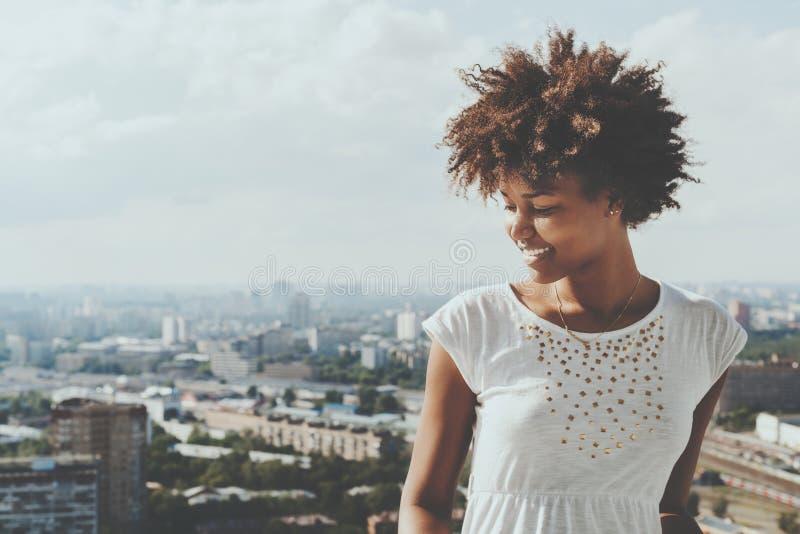 Adolescente femminile riccio sorridente biraziale sul balcone fotografia stock