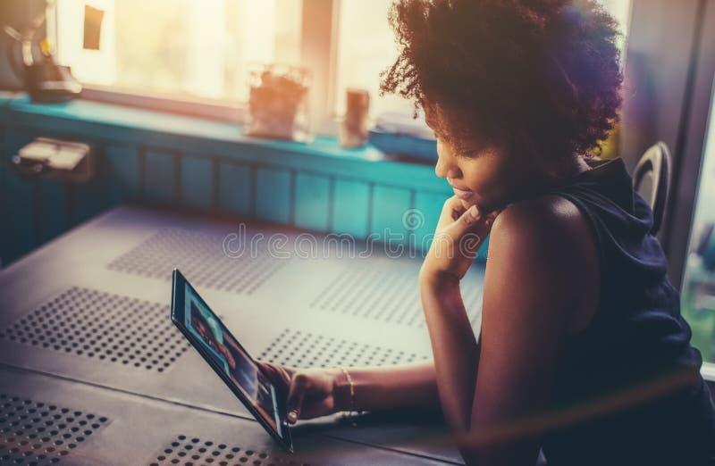 Adolescente femminile riccio sveglio brasiliano con la compressa digitale immagine stock libera da diritti