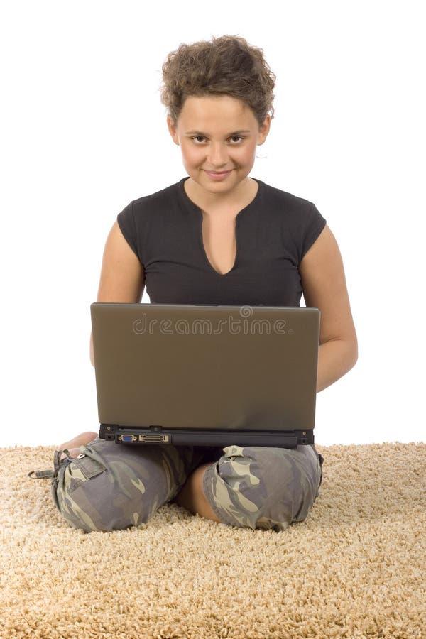 Adolescente femminile sulla moquette con il computer portatile fotografia stock