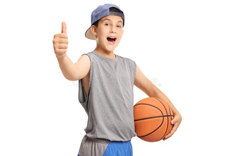 Adolescente fresco com um basquetebol que mostra os polegares acima fotografia de stock royalty free