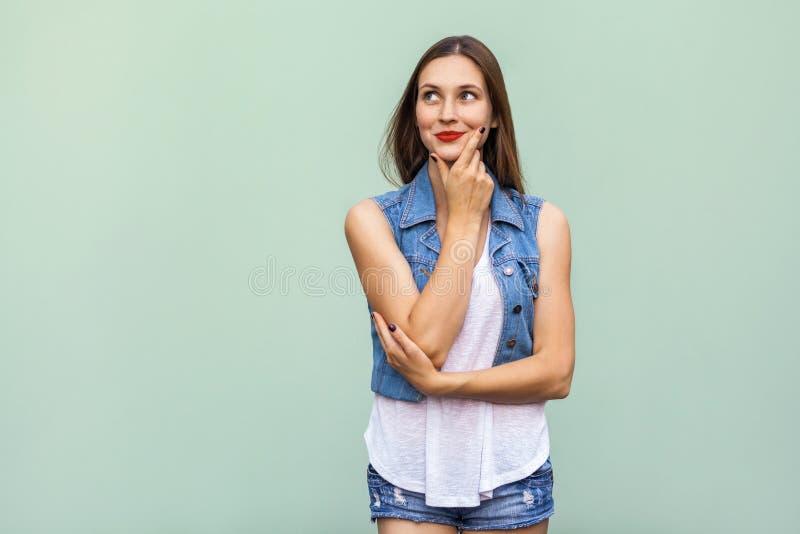 Adolescente gaie heureuse avec les taches de rousseur, le T-shirt de style occasionnel et la veste blancs de jeans, recherchant,  images libres de droits