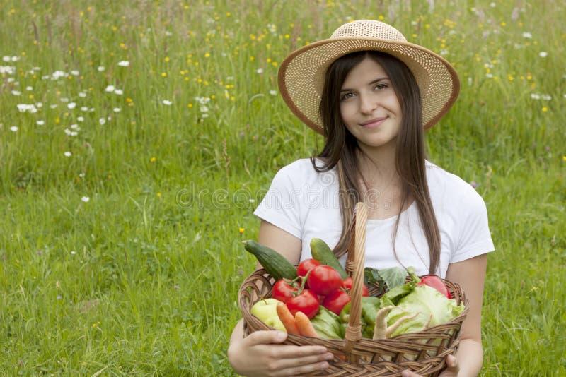 Adolescente grazioso che tiene un cestino delle verdure fotografia stock