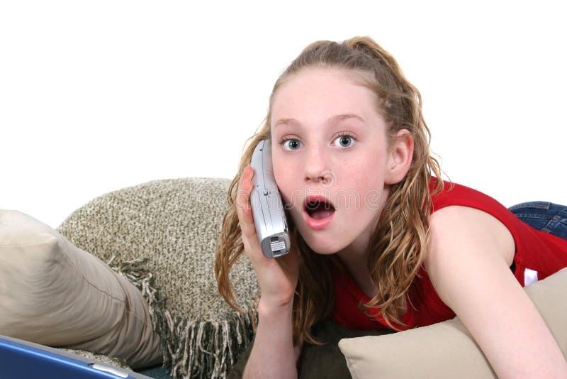 Adolescente hermoso en el teléfono celular que mira Skocked imagen de archivo libre de regalías
