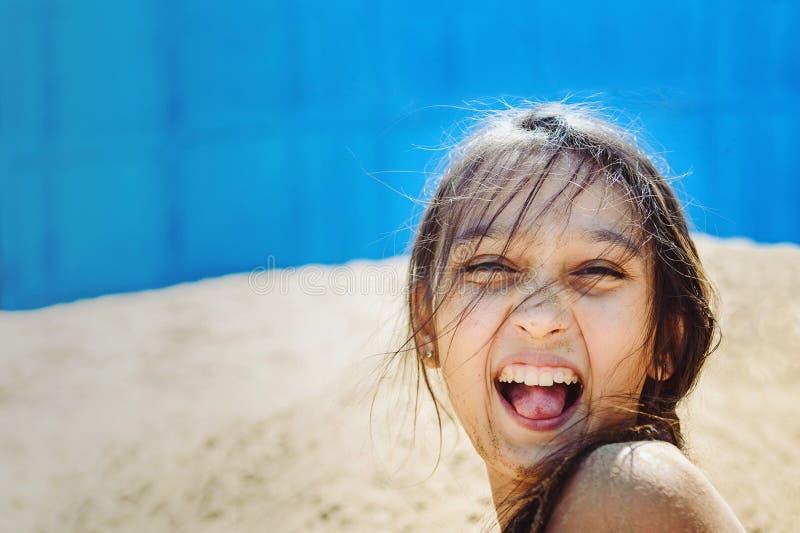 Adolescente hermoso en la arena con el pelo oscuro mojado que ríe en alta voz en la playa en un día soleado del verano fotografía de archivo libre de regalías