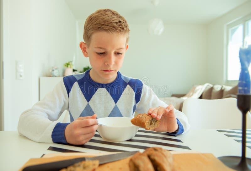 Adolescente hermoso que come la sopa y el pan entero del grano en sala de estar brillante imagen de archivo