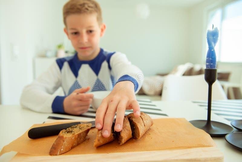 Adolescente hermoso que come la sopa y el pan entero del grano en sala de estar brillante imagen de archivo libre de regalías