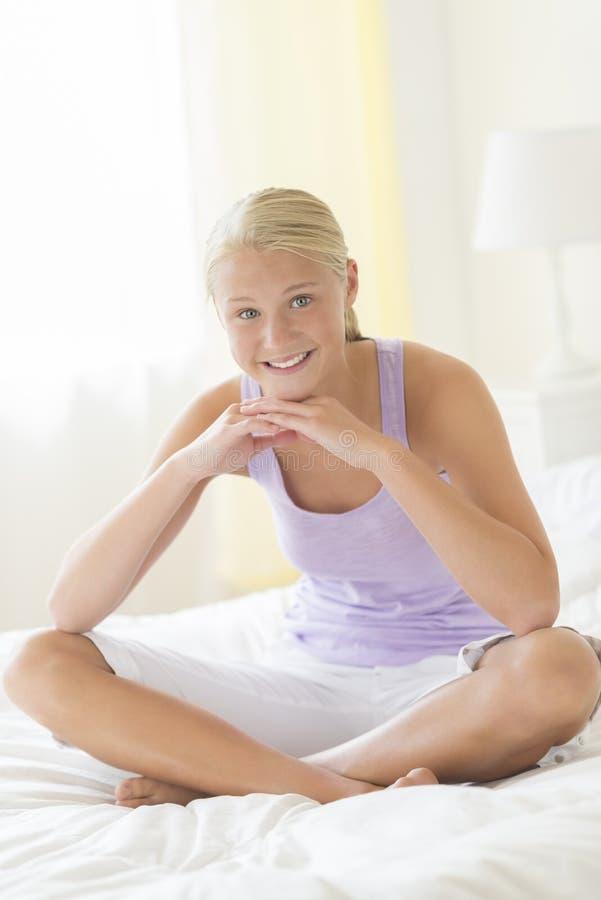 Adolescente hermoso que se sienta en cama imagenes de archivo