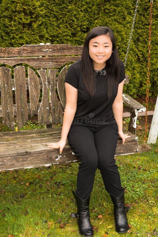 Adolescente hermoso que se sienta en el oscilación de madera imagen de archivo