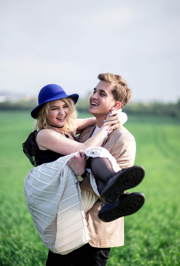Adolescente hermoso que se sostiene y que levanta encima de su novia fotografía de archivo libre de regalías
