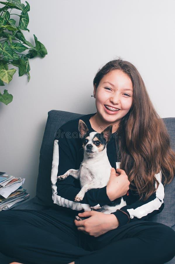 Adolescente heureuse avec l'accolade ? la maison avec le chien photo libre de droits