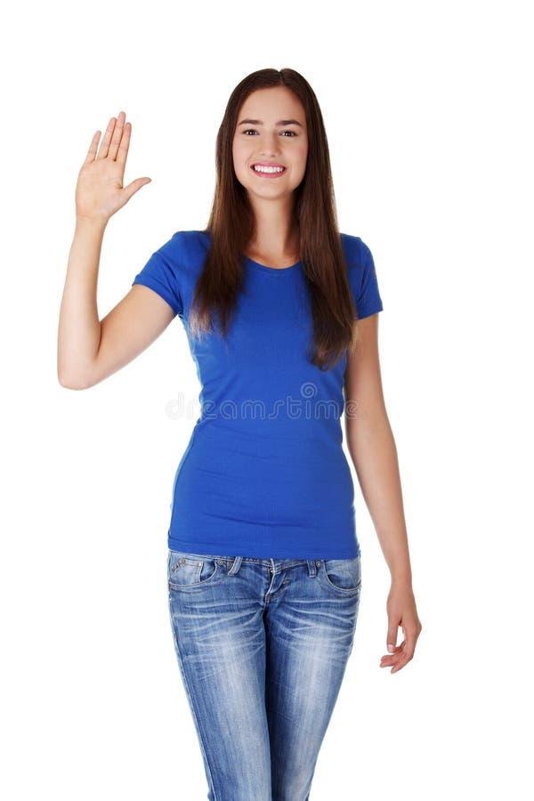 Adolescente heureuse ondulant une salutation photo libre de droits