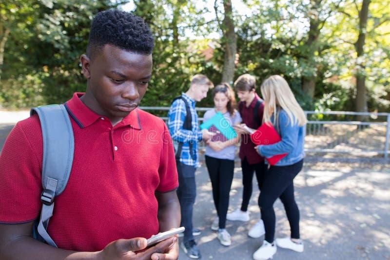 Adolescente infeliz que es tiranizado por el mensaje de texto en la escuela foto de archivo libre de regalías