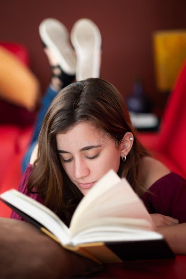 Adolescente ispano che legge un libro a casa immagini stock libere da diritti