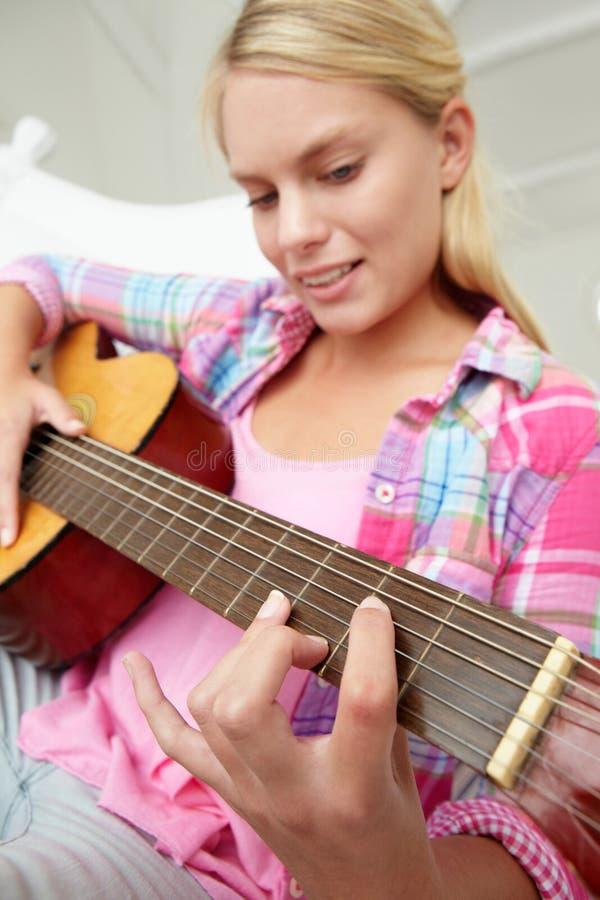 Adolescente jouant la guitare acoustique images stock