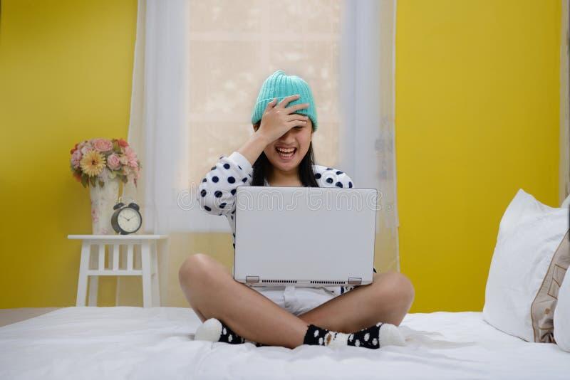 Adolescente joven feliz con el ordenador portátil imagen de archivo