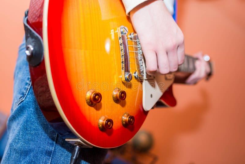 Adolescente joven que juega en la guitarra eléctrica, foco en el botón de tono imagenes de archivo