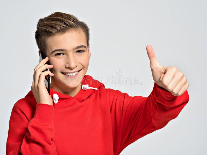 Adolescente joven que llama por el teléfono móvil imagen de archivo