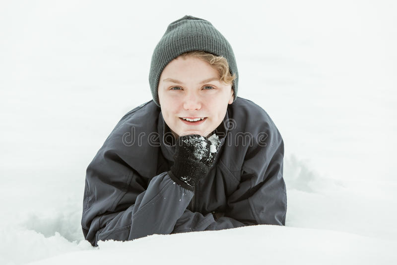 Adolescente joven que miente en nieve el día de invierno fotografía de archivo