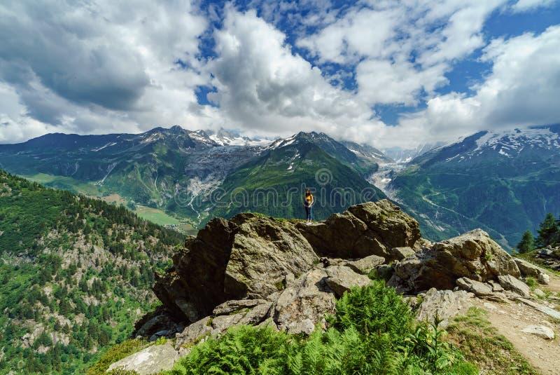 Adolescente joven que presenta en piedra grande en las montañas imagen de archivo