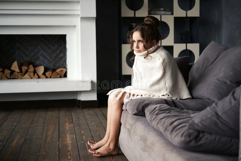 Adolescente joven que se sienta en el sofá fotografía de archivo