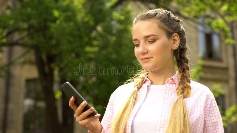 Adolescente joven que usa smartphone, esperando en la parada de autobús, jugando al juego en línea imágenes de archivo libres de regalías