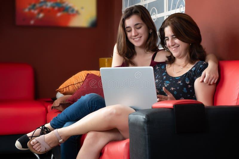 Adolescente latino-americano e sua mãe que usa um portátil em casa fotografia de stock royalty free
