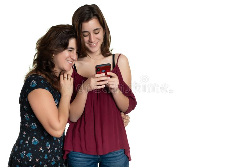Adolescente latino-americano e sua m?e afetuosa que olham um smartphone imagem de stock royalty free