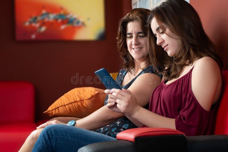 Adolescente latino-americano e sua m?e que olham um smartphone imagem de stock royalty free