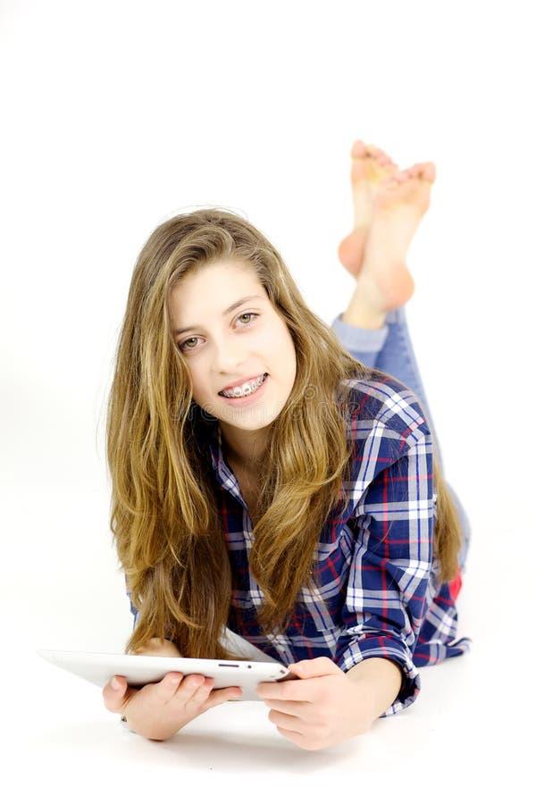 Adolescente lindo con el pelo largo que sonríe con la tableta imagenes de archivo