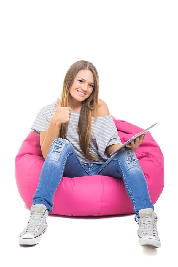 Adolescente lindo con la tableta que gesticula los pulgares para arriba imagen de archivo libre de regalías
