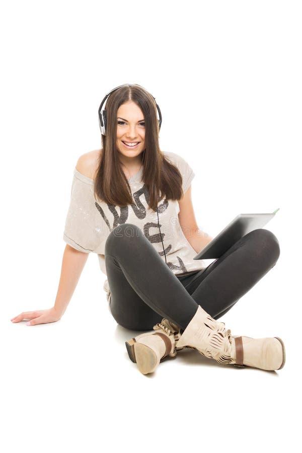 Adolescente lindo con música que escucha de la tableta en los auriculares foto de archivo