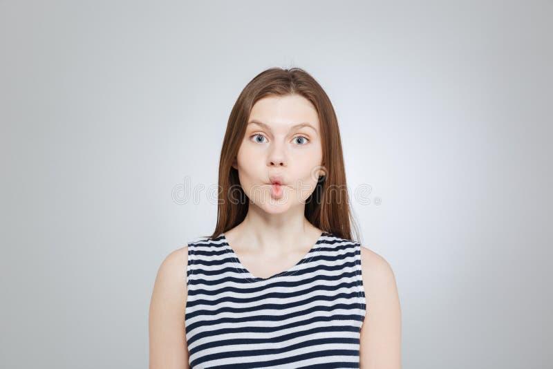 Adolescente lindo graciosamente en el top rayado que hace la cara divertida imagen de archivo