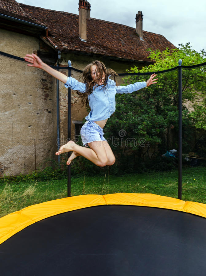 Adolescente lindo que salta en el trampolín fotografía de archivo libre de regalías