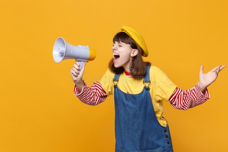 Adolescente loco de la muchacha en los sundress franceses de la boina y del dril de algodón que miran a un lado, grito en megáfon foto de archivo