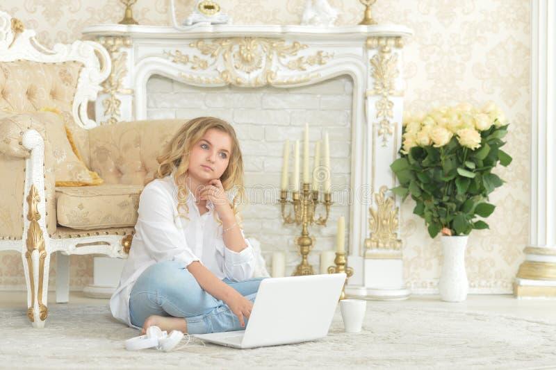 Adolescente louro encaracolado na roupa ocasional que senta-se no assoalho fotos de stock