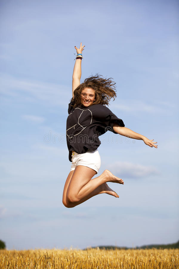 Adolescente louro feliz de salto imagem de stock