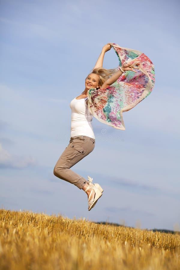 Adolescente louro feliz de salto fotos de stock