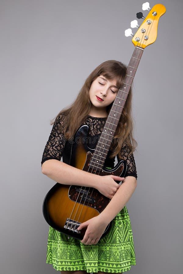 Adolescente louro que abraça a guitarra-baixo fotografia de stock