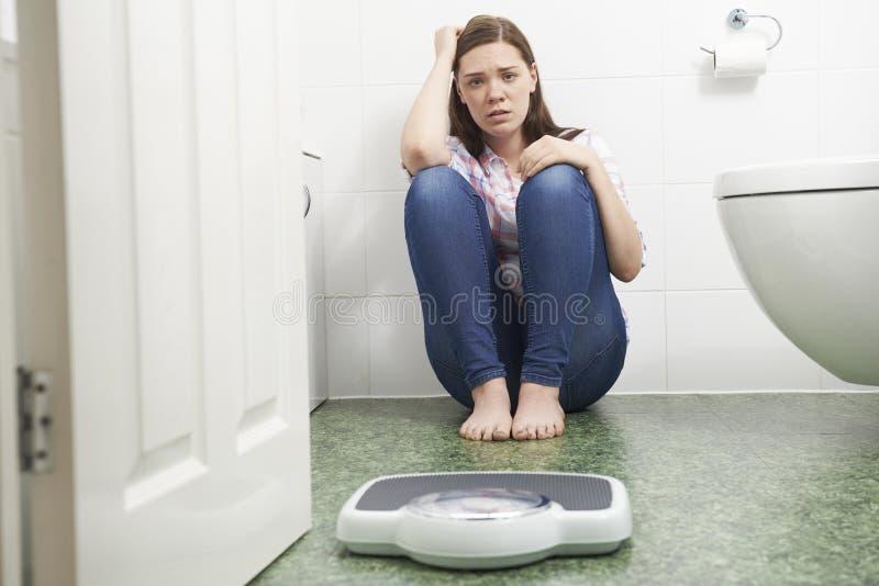 Adolescente malheureuse s'asseyant sur le plancher regardant des échelles de salle de bains image stock