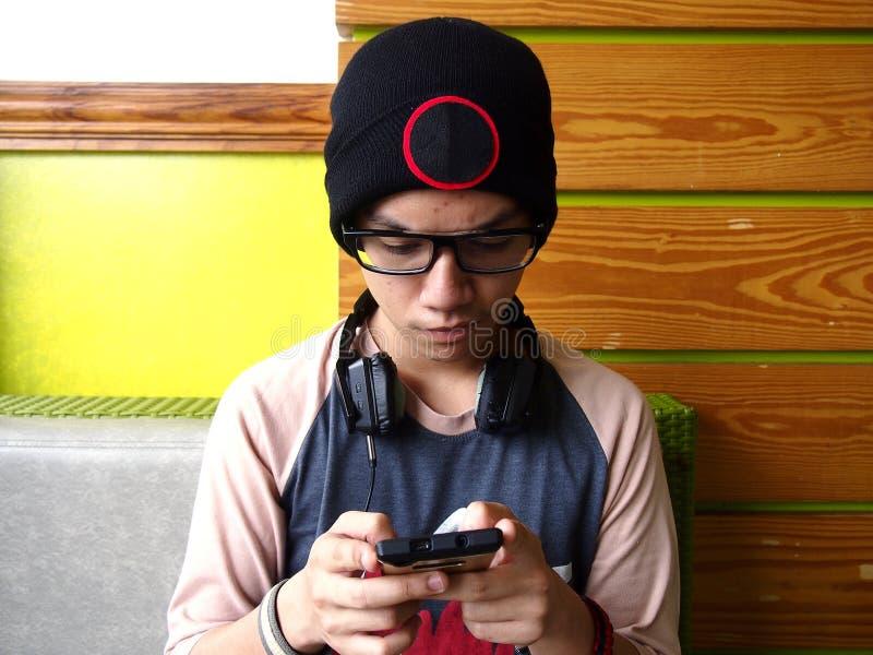 Adolescente maschio dell'anca che per mezzo di uno smartphone fotografia stock