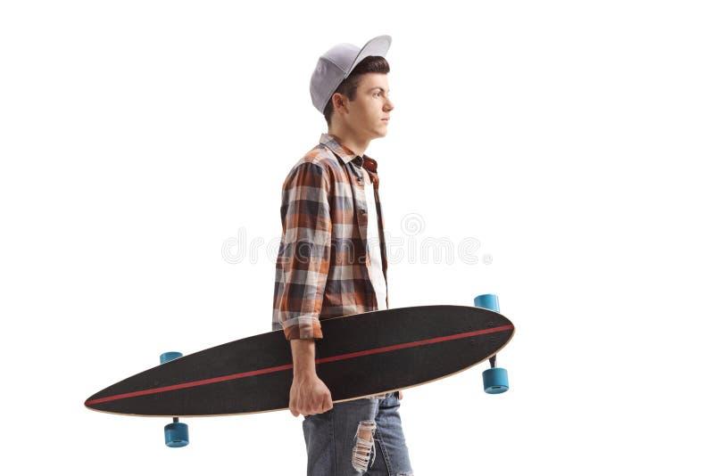 Adolescente masculino com uma posição do longboard foto de stock royalty free