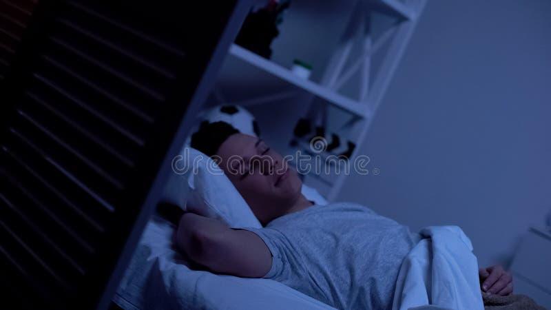 Adolescente masculino que dorme no quarto confortável, nivelando para relaxar após o dia longo imagem de stock royalty free