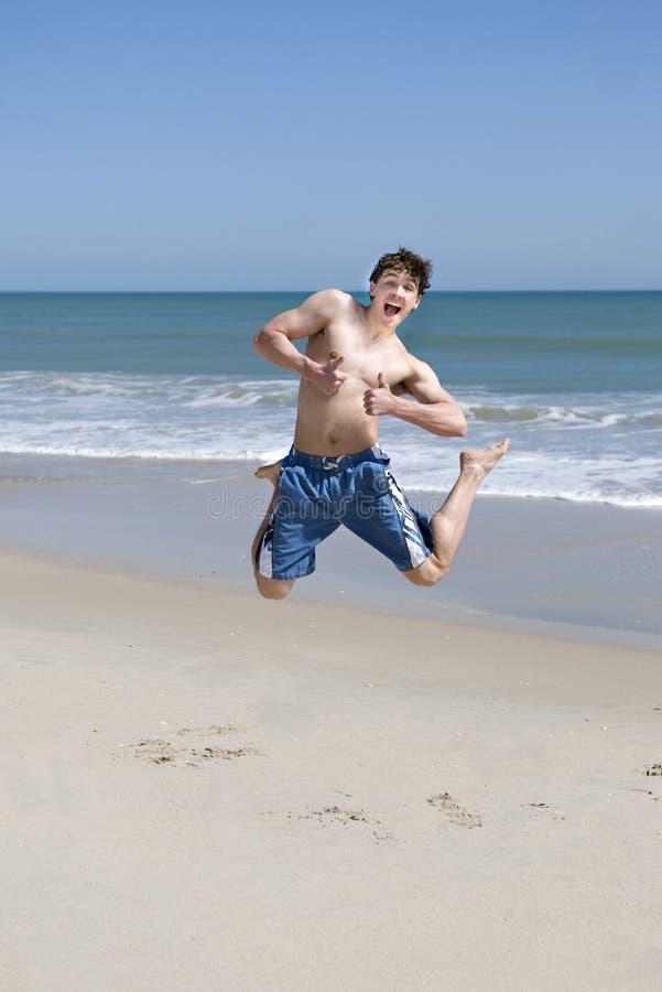 Adolescente masculino que salta na praia fotos de stock