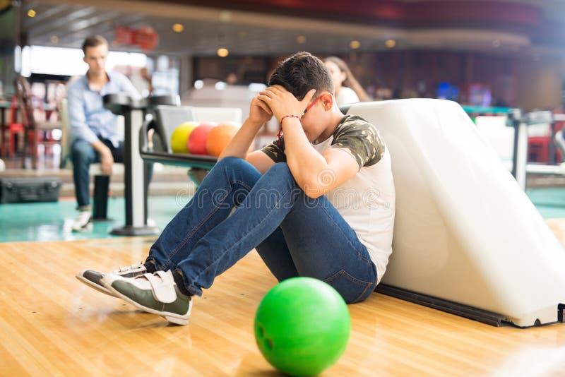 Adolescente masculino triste que se sienta en la bolera en club imagen de archivo