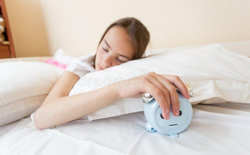 Adolescente mettant le réveil de sonnerie sous l'oreiller image stock