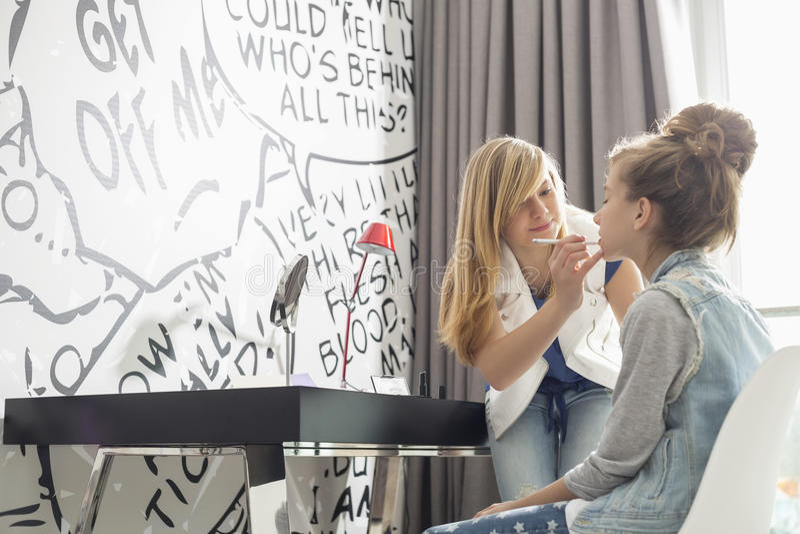 Adolescente mettant le rouge à lèvres sur la soeur à la maison image libre de droits